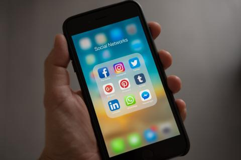 Image of a hand holding a phone showing social media apps