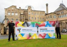 Councillor Pearson and Roy Thompson from Heineken Brewery Holding the Yorkshire 2019 para-cycling flag