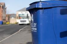 Blue wheelie bin with bin wagon driving along street
