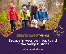 Image of a family with a dog walking through a woods in Selby district