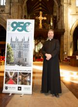 Selby Abbey vicar John Weetman stood with a selby950 banner in the Selby Abbey