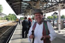Walking tour participant dressed as a shopkeeper with a train station in the background