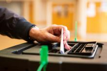 Image shows a vote being put in a sealed ballot box